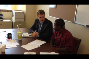 Street Court coordinator Chris Martin (left) helping a client with paperwork.